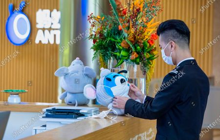 A security guard adjusts the mask on Ant mascot in the Ant Group headquarters in Hangzhou, China, 27 September 2020 (issued 28 September 2020). Ant Group is the parent company of China's largest mobile payments business Alipay and leading provider of financial services technology. The Alipay mobile application serves over 1 billion annual active users, according to the company. Ant Group was founded by billionaire Jack Ma, and has announced it will aim for a 30 billion US dollar initial public offering (IPO) latter this year.