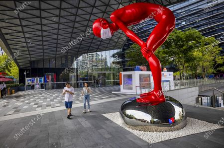 People walk past a sculpture at the main entrance in the Ant Group headquarters in Hangzhou, China, 27 September 2020 (issued 28 September 2020). Ant Group is the parent company of China's largest mobile payments business Alipay and leading provider of financial services technology. The Alipay mobile application serves over 1 billion annual active users, according to the company. Ant Group was founded by billionaire Jack Ma, and has announced it will aim for a 30 billion US dollar initial public offering (IPO) latter this year.