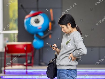 A woman uses her phone in front of the Ant Group headquarters in Hangzhou, China, 27 September 2020 (issued 28 September 2020). Ant Group is the parent company of China's largest mobile payments business Alipay and leading provider of financial services technology. The Alipay mobile application serves over 1 billion annual active users, according to the company. Ant group is an affiliate company of the Alibaba Group founded by billionaire Jack Ma and it is preparing a simultaneous initial public offering (IPO) in Hong Kong and Shanghai.