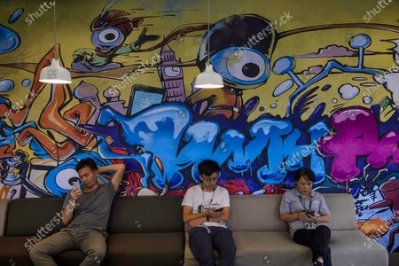 People sit beneath a mural on the wall in an office within the Ant Group headquarters in Hangzhou, China, 27 September 2020 (issued 28 September 2020). Ant Group is the parent company of China's largest mobile payments business Alipay and leading provider of financial services technology. The Alipay mobile application serves over 1 billion annual active users, according to the company. Ant group is an affiliate company of the Alibaba Group founded by billionaire Jack Ma and it is preparing a simultaneous initial public offering (IPO) in Hong Kong and Shanghai.