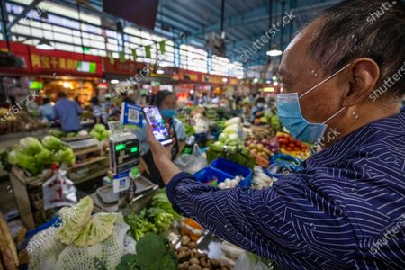 A man scans an Alipay QR payment code while shopping at a wet market, close to the Ant Group headquarters in Hangzhou, China, 27 September 2020 (issued 28 September 2020). Ant Group is the parent company of China's largest mobile payments business Alipay and leading provider of financial services technology. The Alipay mobile application serves over 1 billion annual active users, according to the company. Ant group is an affiliate company of the Alibaba Group founded by billionaire Jack Ma and it is preparing a simultaneous initial public offering (IPO) in Hong Kong and Shanghai.
