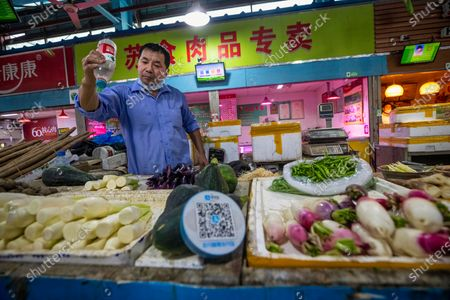A man sells vegetables at a wet market, with a Alipay QR payment code displayed at his booth, close to the Ant Group headquarters in Hangzhou, China, 27 September 2020 (issued 28 September 2020). Ant Group is the parent company of China's largest mobile payments business Alipay and leading provider of financial services technology. The Alipay mobile application serves over 1 billion annual active users, according to the company. Ant group is an affiliate company of the Alibaba Group founded by billionaire Jack Ma and it is preparing a simultaneous initial public offering (IPO) in Hong Kong and Shanghai.