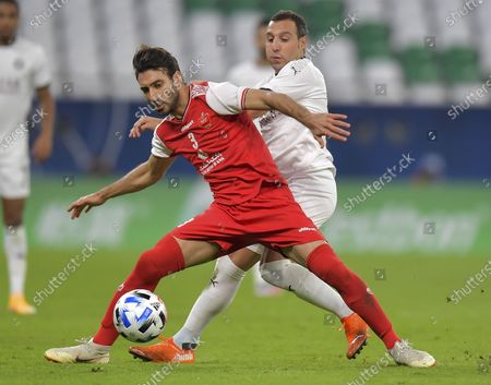 Stock Picture of Santi Cazorla (R) of Al Sadd SC vies for the ball with Shojae Khalilzadeh of Persepolis FC during the AFC Asian Champions League round of 16 football match between Persepolis FC of Iran and Al Sadd SC of Qatar at Al Education City Stadium in Doha, Capital of Qatar, Sept. 27, 2020.