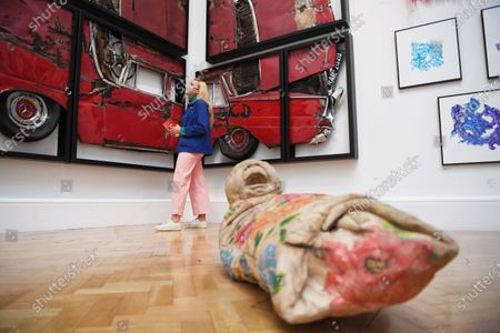A masked staff member poses with the work 'Oh Lord, Why You Buy Me?' by Ron Arad during a photocall for the 252nd Summer Exhibition at the Royal Academy of Arts in London, Britain, 28 September 2020. Due to the coronavirus pandemic for the first time in the history, the Summer Exhibition will take place in the autumn. Over 1000 works in a range of media, by emerging and established artists, feature in the exhibition. Summer Exhibition at the Royal Academy of Arts, London, runs from 06 October 2020 to 03 January 2021.
