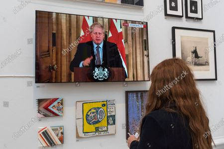 """A staff member views a digital video of Boris Johnson addressing the nation, """"Twice"""" by John SMith. Preview of the Summer Exhibition at the Royal Academy of Arts in Piccadilly which, due to the Covid-19 lockdown, is taking place for the first time in the autumn. Over 1000 works in a range of media by Royal Academicians, established and emerging artists, feature in the exhibition which runs from 6 October 2020 - 3 January 2021."""