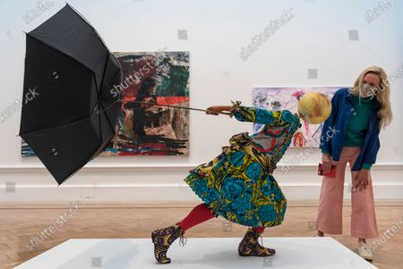 """A staff member poses with """"Air Kid (Girl)"""" by Yinka Shonibare RA. Preview of the Summer Exhibition at the Royal Academy of Arts in Piccadilly which, due to the Covid-19 lockdown, is taking place for the first time in the autumn. Over 1000 works in a range of media by Royal Academicians, established and emerging artists, feature in the exhibition which runs from 6 October 2020 - 3 January 2021."""