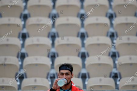 Empty seats are seen in the background as Italy's Fabio Fognini drinks during the first round match of the French Open tennis tournament against Kazakhstan's Mikhail Kukushkin at the Roland Garros stadium in Paris, France