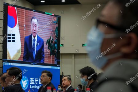 Chinese Foreign Minister Wang Yi, centre, and attendees wearing face masks to help curb the spread of the coronavirus listen to a speech by former U.N. Secretary-General Ban Ki-moon on a screen during the Lanting Forum on the International Order and Global Governance in the Post COVID-19 Era held at the Ministry of Foreign Affairs office in Beijing, . Even though the spread of COVID-19 has been all but eradicated in China, the pandemic is still surging across the globe with ever rising death toll