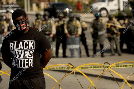 LOS ANGELES, CA - SEPTEMBER 23, 2020 - A protester stands close to sheriff deputies near the South L.A. Sheriff's Station protesting the fatal shootings of Dijon Kizzee, Anthony Guardado and Anthony Weber on W. Imperial Highway in Los Angeles on September 27, 2020. The demonstration was led by the Coalition for Community Control Over the Police. The protesters were also joined by Guardado's father Cristobal Guardado and Kizzee's aunt Sequarier McCoy. (Genaro Molina / Los Angeles Times)