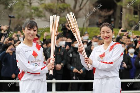 File photo taken on Feb. 15, 2020 shows that Tokyo 2020 Torch Relay Official Ambassador Ishihara Satomi (R) rehearses passing the Olympic flame to a stand-in torchbearer during the Torch Relay rehearsal in Hamura, Tokyo, Japan. The route and schedule of the torch relay for the postponed Tokyo Olympic and Paralympic Games will remain as originally planned, the Tokyo 2020 organizers announced on Sept. 28, 2020.