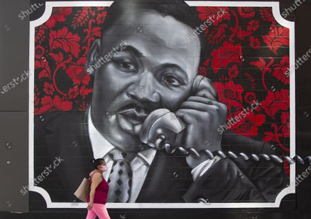 A woman walks past a recently unveiled mural of Dr. Martin Luther King Jr., titled 'Roxbury Love Story' in Boston, Massachusetts, USA, 28 September 2020. The mural, showing Dr King and his wife Coretta Scott King, is on a building near the site of the former 12th Baptist Church where King preached in the 1950's while living in Boston.