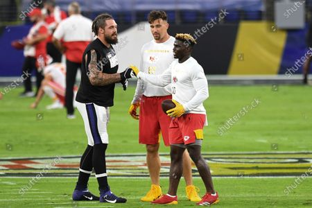 Baltimore Ravens defensive end Derek Wolfe (left) greets Kansas City Chiefs tight end Travis Kelce (center) and Kansas City Chiefs wide receiver Tyreek Hill (right) before an NFL football game, in Baltimore