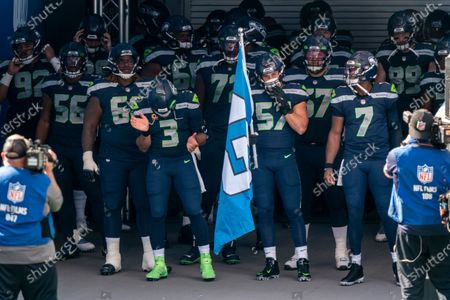 Seattle Seahawks including Bryan Mone (92), Jordyn Brooks (56). Damien Lewis (68), Russell Wilson (3) Brandon Shell (72), Cody Barton and Geno Smith (7) wait to take the field before an NFL football game against the Dallas Cowboys, in Seattle. The Seahawks won 38-31