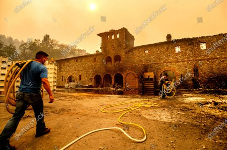 Stock Picture of Winery workers Carlos Perez, left, and Jose Juan Perez extinguish hotspots at Castello di Amorosa, in Calistoga, Calif., which was damaged in the Glass Fire