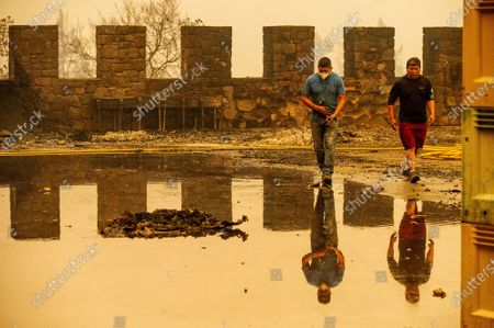 Winery worker Carlos Perez, left, walks, in Calistoga, Calif., through Castello di Amorosa, which was damaged in the Glass Fire. Perez helped build the wine cellar that was scorched in the blaze