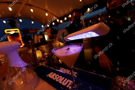 Stock Picture of A man disinfects a cup with ultra-violet light as preventative measure against coronavirus at a restaurant in Panama City, Panama, 28 September 2020.