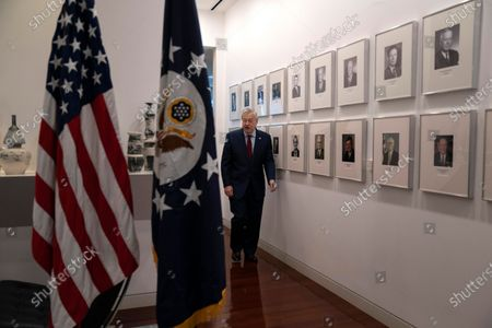 Ambassador to China Terry Branstad walks past a photo wall of previous U.S. ambassadors to China before an interview at the U.S. embassy in Beijing on . The departing U.S. ambassador on Tuesday defended a tough approach to China that has riled relations between the world's two largest economies, saying the Trump administration has made progress on trade and that he hopes it will extend to other areas