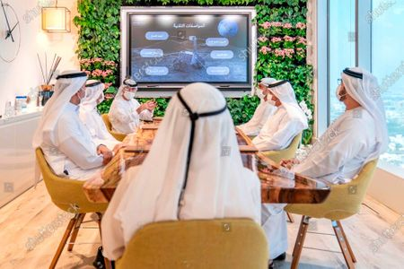 In this photo made available from the twitter account of UAE Vice President and Prime Minister and ruler of Dubai, Emirati officials brief Sheikh Mohammed bin Rashid Al Maktoum about a possible moon mission, in Dubai, United Arab Emirates. Sheikh Mohammed made the announcement Tuesday on Twitter that his country plans to send an unmanned spacecraft to the moon in 2024