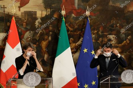 Italian Premier Giuseppe Conte and Swiss Confederation President Simonetta Sommaruga adjust their face masks, used to prevent the spread of COVID-19, during their joint press conference following their meeting at Chigi Palace, in Rome