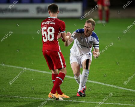 Ben Woodburn of Liverpool helps Mark Ellis of Tranmere Rovers