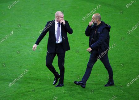 Burnley manger Sean Dyche and counterpart Pep Guardiola of Manchester City cover their mouths as they talk at half time