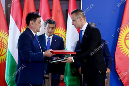 Kyrgyz President Sooronbay Jeenbekov (C) looks on as Minister of Foreign Affairs and Trade Peter Szijjarto (R) and Sanzhar Mukanbetov, Kyrgyz Minister of Economy (L) sign a bilateral agreement on the digitalization of the economy and on the mutual protection of investments at the Carmelite Monastery in Budapest, Hungary, 29 September 2020.