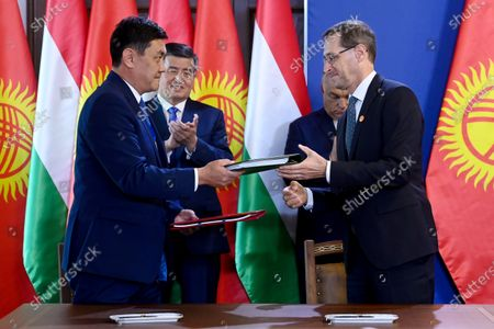 Hungarian Minister of Finance Mihaly Varga (R) and Sanzhar Mukanbetov Kyrgyz (L) Minister of Economy hand over documents to each other after signign a bilateral agreement on the pevention of double taxation and of tax evasion at the Carmelite Monastery in Budapest, Hungary, 29 September 2020.