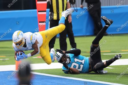Stock Picture of Los Angeles Chargers running back Austin Ekeler (30) leaps into the end zone over Carolina Panthers outside linebacker Jeremy Chinn (21) for a touchdown during an NFL football game, in Inglewood, Calif