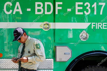 Stock Photo of Victor Alvarez, from San Bernardino National Forest, watches memorial service for fallen USDA Forest Service firefighter Charles Edward Morton on his mobile phone at the Rock Church on Friday, Sept. 25, 2020 in San Bernardino, CA. (Irfan Khan / Los Angeles Times)
