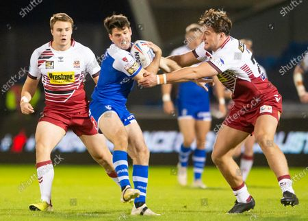 St Helen's Lachlan Coote evades the tackle of Wigan's Liam Byrne.