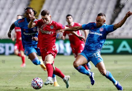 Marinos Tzionis (C) of Omonoia Nicosia in action against Rafinha (R) and Ruben Semedo (L) of Olympiacos FC during the UEFA Champions League playoff 2nd leg soccer match between Omonoia Nicosia vs Olympiacos FC at the GSP stadium in Nicosia, Cyprus, 29 September 2020.