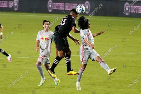 Inter Miami midfielder Victor Ulloa (13) heads the ball as New York Red Bulls forward Brian White, left, and midfielder Omir Fernandez defend during the first half of an MLS soccer match, in Fort Lauderdale, Fla