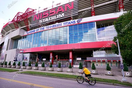 Cyclist passes by Nissan Stadium, home of the Tennessee Titans, in Nashville, Tenn. The Titans suspended in-person activities through Friday after the NFL says three Titans players and five personnel tested positive for the coronavirus, becoming the first COVID-19 outbreak of the NFL season in Week 4