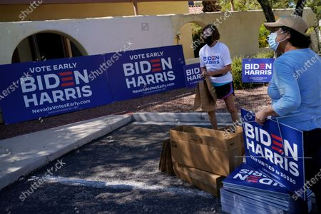 Volunteer Carolyn Barnes, left, hands out campaign masks, signs and shirts in support of presidential candidate Joe Biden at a drive-thru station, in Las Vegas