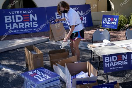 Volunteer Carolyn Barnes hands out campaign face masks, signs and shirts in support of Democratic presidential candidate Joe Biden at a drive-thru station, in Las Vegas
