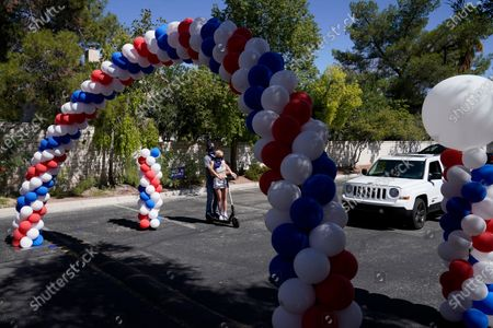 President Donald Trump supporters ride a scooter through a campaign swag drive-thru for Democratic presidential candidate Joe Biden, in Las Vegas