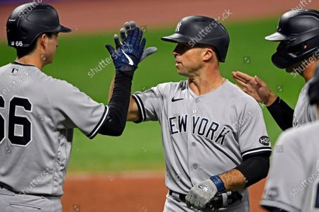 New York Yankees' Brett Gardner (11) is congratulated by Kyle Higashioka, left, and Gleyber Torres after hitting a two run home run in the seventh inning of Game 1 of an American League wild-card baseball series against the Cleveland Indians, in Cleveland