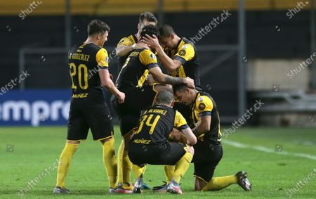 Stock Photo of Jonathan Urretaviscaya of Uruguay's Penarol, center, celebrates scoring his side's third goal against Chile's Colo Colo with teammates during a Copa Libertadores soccer match in Montevideo, Uruguay