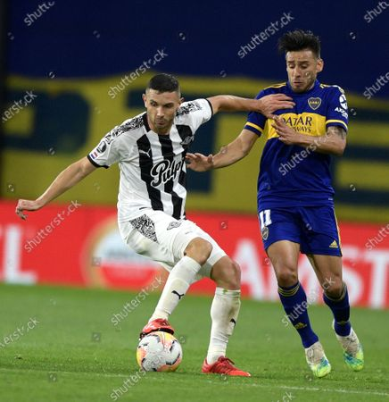 Adrian Martinez of Paraguay's Libertad, left, and Eduardo Salvio of Argentina's Boca Juniors battle for the ball during a Copa Libertadores soccer match in Buenos Aires, Argentina