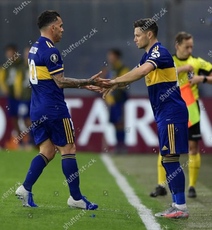Carlos Tevez of Argentina's Boca Juniors, left, greets teammate Mauro Zarate who replaced him in the second half of a Copa Libertadores soccer match against Paraguay's Libertad in Buenos Aires, Argentina