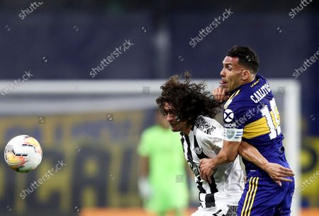 Blas Caceres of Paraguay's Libertad, left, and Carlos Tevez of Argentina's Boca Juniors battle for the ball during a Copa Libertadores soccer match in Buenos Aires, Argentina