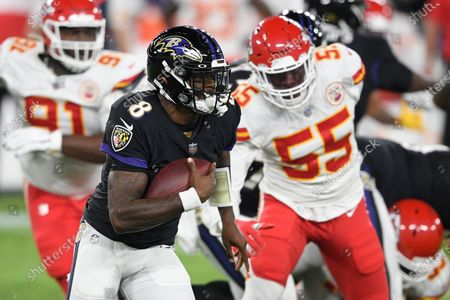 Baltimore Ravens quarterback Lamar Jackson (8) runs with the ball during the first half of an NFL football game against the Kansas City Chiefs defensive end Frank Clark (55), in Baltimore