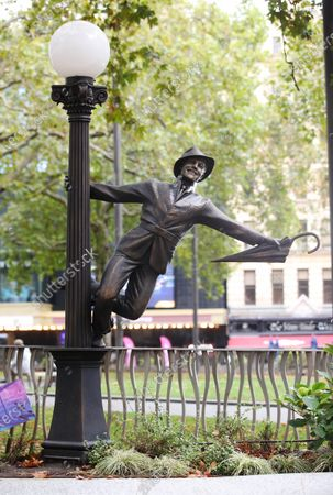 Gene Kelly, one of nine long-term bronze statues in Leicester Square's free to visit Scenes in the Square installation, watches over the square as the trail welcomes its ninth new resident today, Harry Potter on his Nimbus 2000 broomstick, inspired by his debut Quidditch match featured in 'Harry Potter and the Philosopher's Stone'.