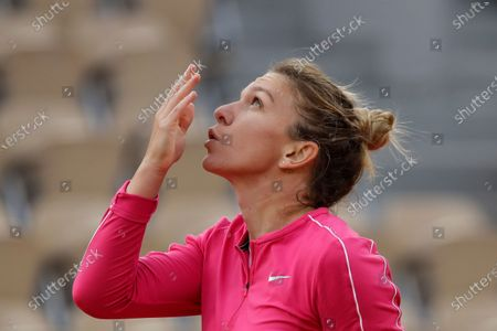 Romania's Simona Halep crosses herself and blows a kiss to the sky after winning her second round match of the French Open tennis tournament against Romania's Irina-Camelia Begu at the Roland Garros stadium in Paris, France