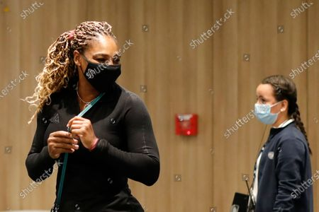 Serena Williams of the U.S., left, leaves after a press conference in which she announced her withdrawal from the tournament because of an Achilles injury prior to her second round match of the French Open tennis tournament at the Roland Garros stadium in Paris, France