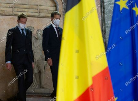 Belgian Minister of Cooperation Development and Finance, Alexander De Croo, right, and Belgian francophone Socialist Party chairman, Paul Magnette walk past a statue prior to a media conference at the Egmont Palace in Brussels, . Almost 500 days after Belgian parliamentary elections, seven parties from both sides of the linguistic border have agreed on forming a fully functioning majority government that will center on dealing with the pandemic and its devastating economic impact