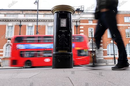 """A Royal Mail postbox painted as part of Black History Month in October, Brixton, London.  It also features """"Queuing at the RA"""" by artist Yinka Shonibare, one of six artists who were commissioned by the Royal Mail to produce original artworks for a set of special stamps issued to mark the 250th anniversary of the Royal Academy (RA)."""