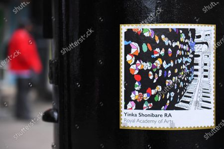 """A Royal Mail postbox painted as part of Black History Month in October, Brixton, London.  It also features """"Queuing at the RA"""" by artist Yinka Shonibare (pictured), one of six artists who were commissioned by the Royal Mail to produce original artworks for a set of special stamps issued to mark the 250th anniversary of the Royal Academy (RA)."""