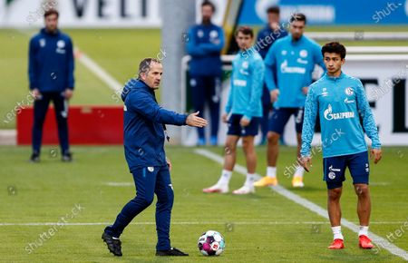 Manuel Baum, new head coach of Bundesliga soccer club FC Schalke 04, left, stands by Schalke's Nick Taitague of the USA, right, during his first training session in Gelsenkirchen, Germany, . The German traditional club dismissed head coach David Wagner after a series of 18 consecutive winless matches last weekend. Former Brazilian defender Naldo is announced as new assistant coach