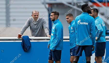 Sport director Jochen Schneider, left, watches forward Ahmed Kutucu during a training session of FC Schalke 04 in Gelsenkirchen, Germany, . The German traditional club dismissed head coach David Wagner after a series of 18 consecutive winless matches last weekend. Manuel Baum is the new head coach, former Brazilian defender Naldo is announced as new assistant coach